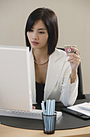 A woman drinks Chinese tea while she works - Asia Images Group