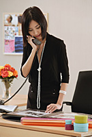 A woman talks on the phone at work - Asia Images Group