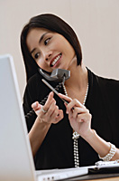 A woman files her nails as she talks on the phone at work - Asia Images Group