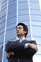 A man with a suit stands in front of a skyscraper - Asia Images Group