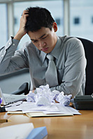 A man looks stressed as he works at his desk - Asia Images Group