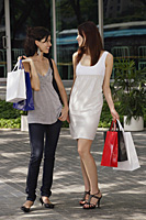 Women with shopping bags, looking at each other - Asia Images Group
