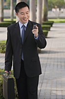 Businessman smiling while looking at mobile phone - Asia Images Group