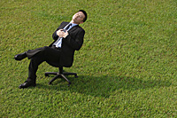 Businessman resting on an office chair - Asia Images Group