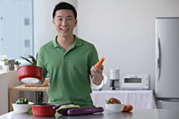 Man cooking and smiling at camera - Asia Images Group