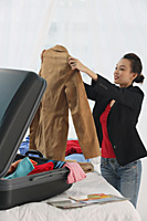 Young woman packing suitcase - Asia Images Group