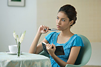 Young woman sitting in restaurant, writing into journal - Asia Images Group