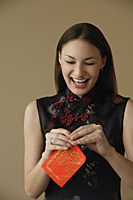 Young woman laughing while opening red envelope - Asia Images Group