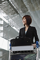 Young woman smiling into distance at the airport - Asia Images Group