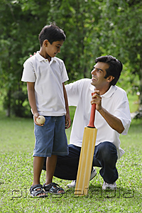 PictureIndia - A father and son play cricket together