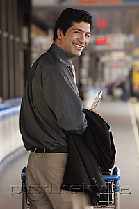 PictureIndia - Man pushing trolley in airport, smiling at camera