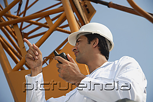 PictureIndia - Man in work uniform pointing and using walkie talkie