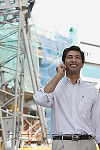 PictureIndia - Man smiling while on mobile phone